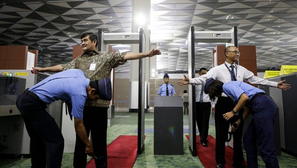 Oficiales de seguridad inspeccionan a los pasajeros en un punto de control de un aeropuerto