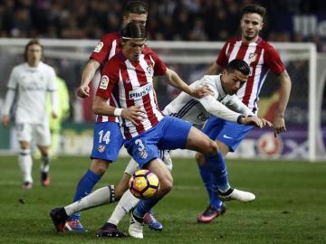 El portugués Cristiano Ronaldo (d), del Real Madrid, lucha el balón con el defensa brasielño del Atlético de Madrid Filipe Luis