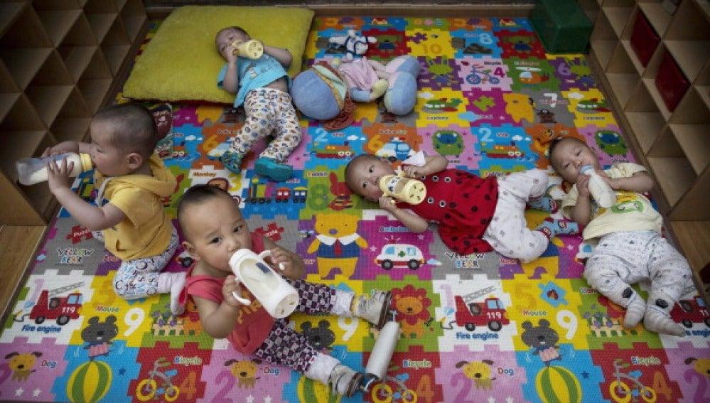 Bebés tomando un biberón con leche