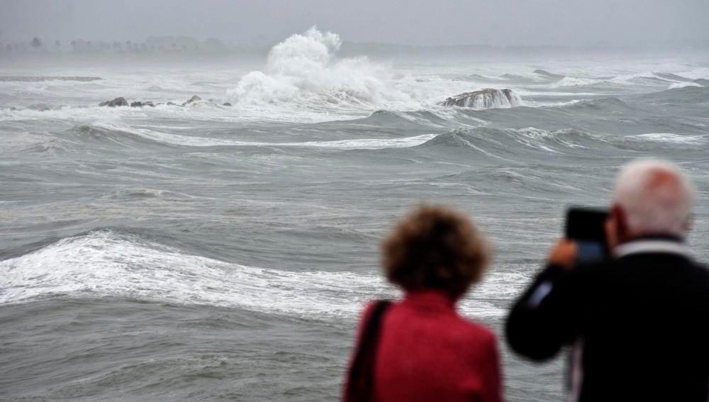 Unos vecinos toman imágenes en una playa afectada por un fuerte temporal.