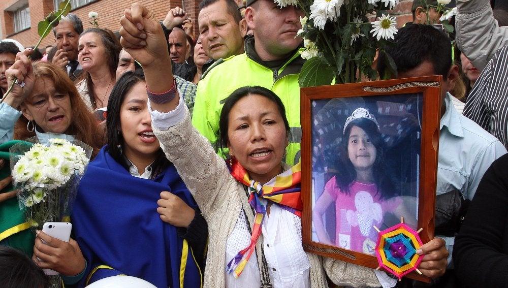 Una mujer sostiene una fotografía de la pequeña asesinada Yuliana Andrea Sambon