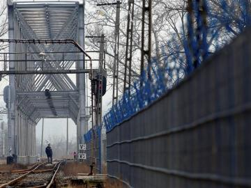 Un policía fronterizo inspecciona una vía de tren