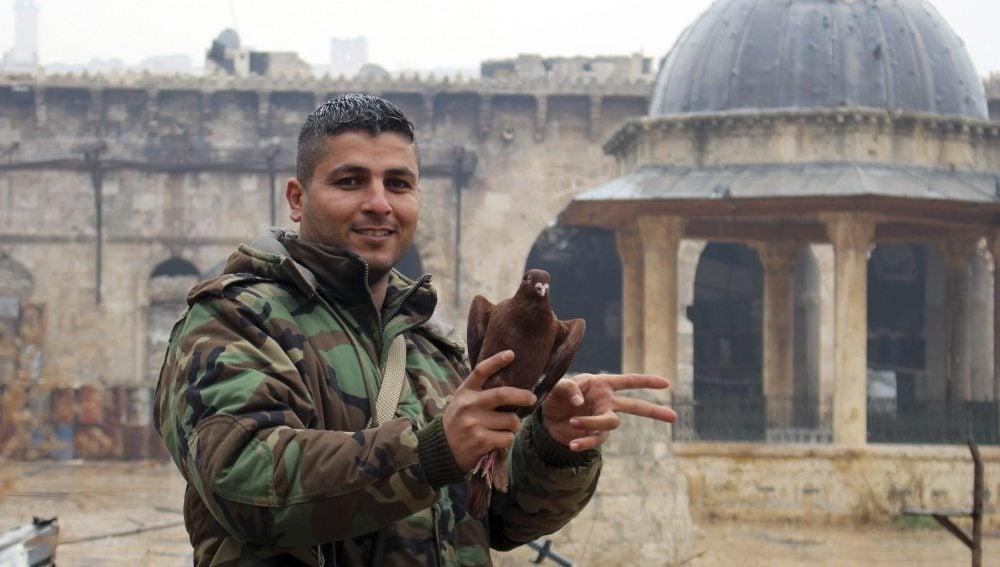 Un soldado sirio hace el símbolo de la victoria junto a la mezquita de Umayyad al este de Alepo