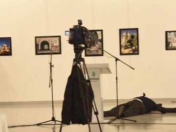 El atacante junto al cuerpo sin vida del embajador ruso en Turquía