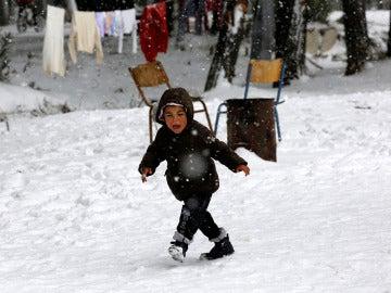 Un niño refugiado caminando sobre la nieve