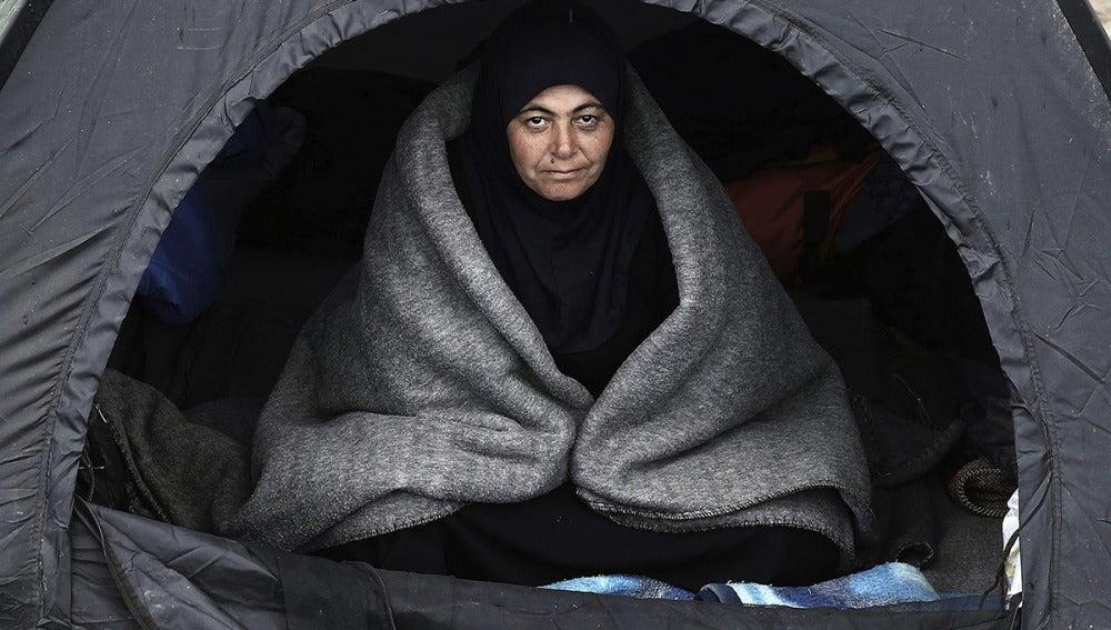 Una refugiada se resguarda del frío en una tienda