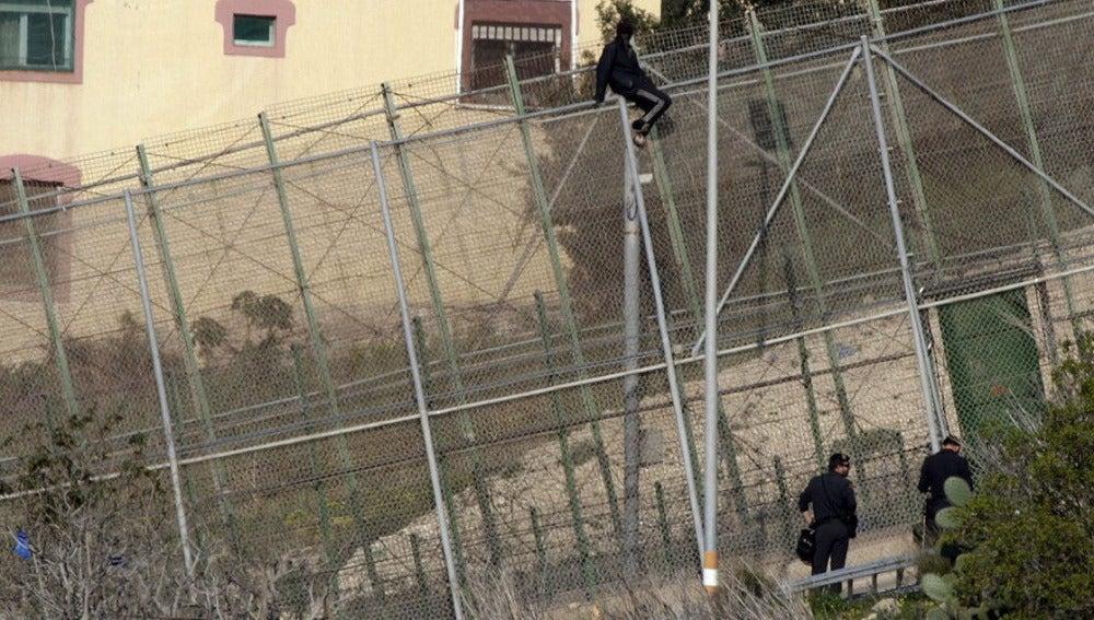Un inmigrante en la zona alta de la valla de Melilla