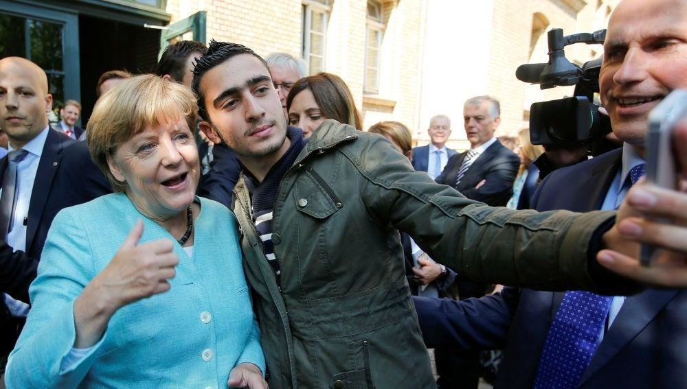 Un refugiado con Angela Merkel