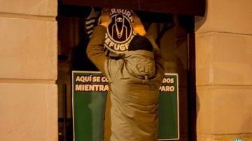 Un hombre colgando carteles en Starbucks