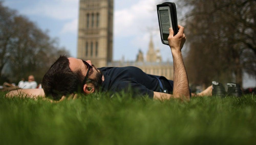 Un lector tumbado leyendo un libro electrónico