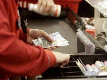 Una cajera de un supermercado devuelve el cambio a un cliente