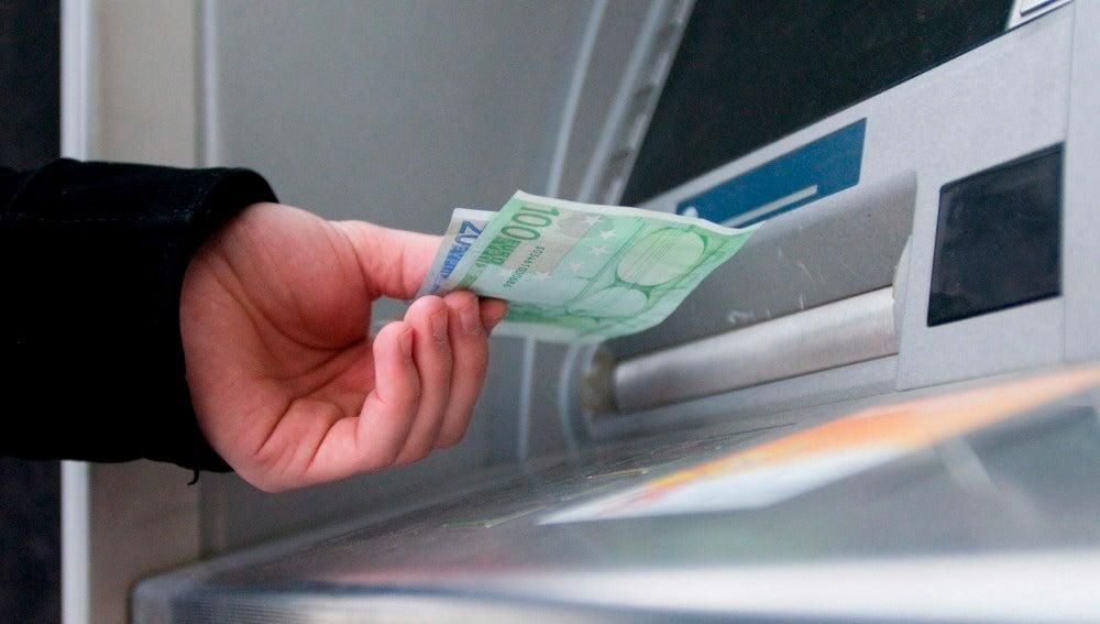 Un hombre saca dinero del cajero automático