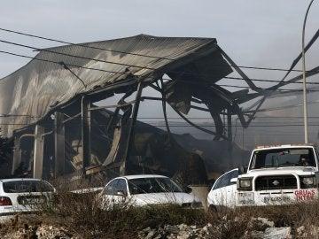 Los bomberos trabajan en la extinción del incendio en una nave de Paterna