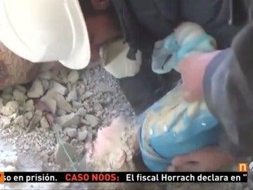 Frame 44.9 de: Voluntarios y vecinos rescatan de entre los escombros a una niña que había quedado sepultada en su casa tras un bombardeo en Siria