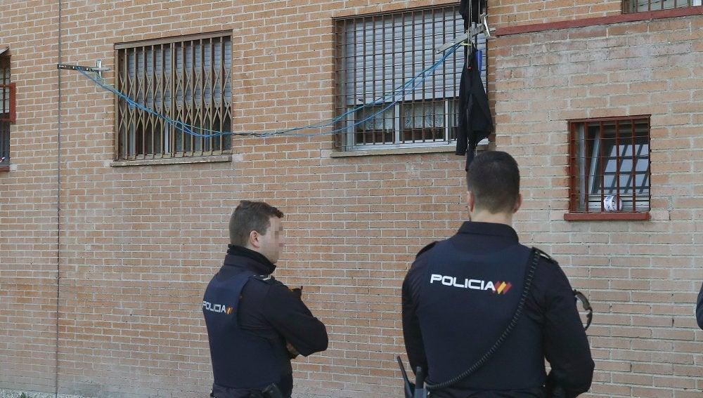 Dos agentes ante el lugar en el que cayó desde una ventana a una altura de cinco metros una mujer herida muy grave en el barrio madrileño de Usera