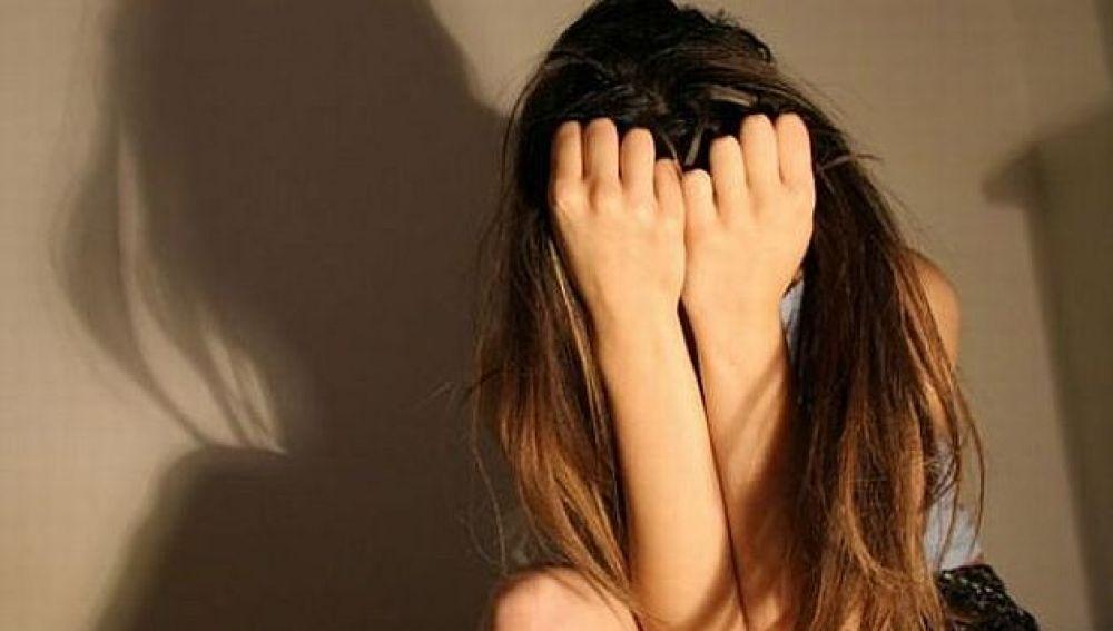Una joven tapándose la cara