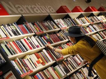 Una mujer mira libros en los estanterías de una librería