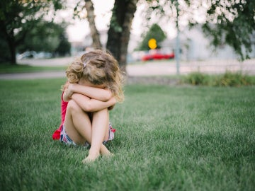 Una niña pequeña llora sentada en el suelo.