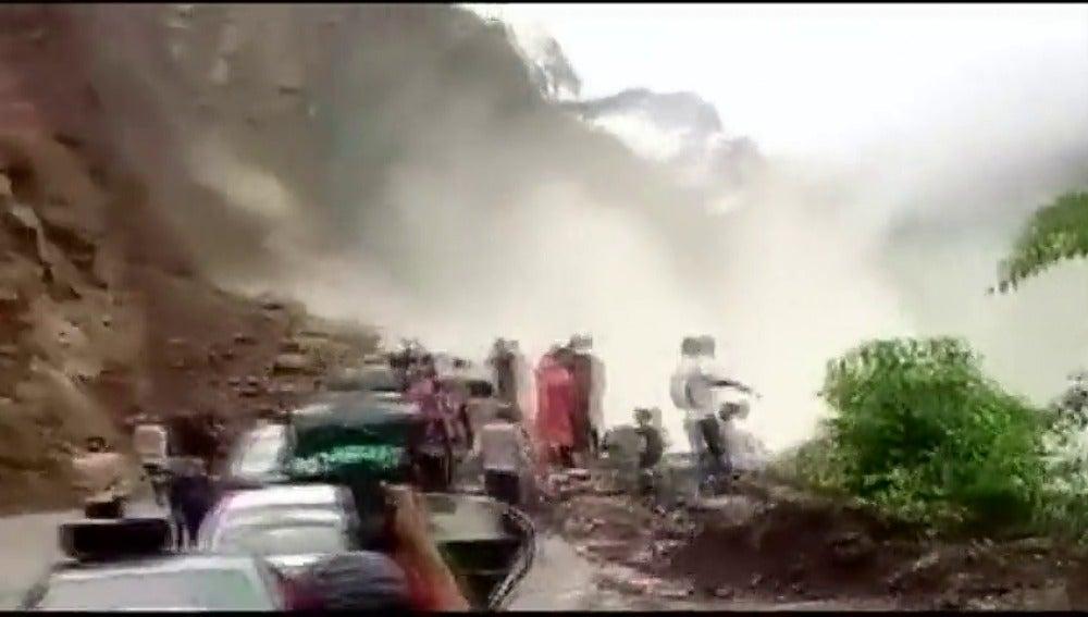 Frame 5.107555 de: Desprendimiento de rocas y tierra sobre una carretera transitada por el agua acumulada