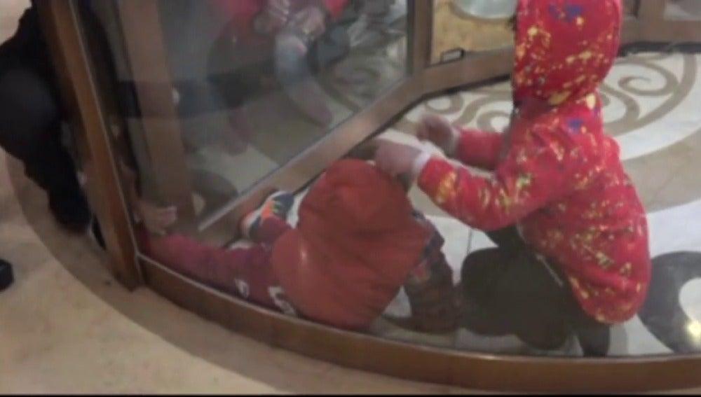 Frame 4.987843 de: Dos niños han sido rescatados al quedarse atrapados en una puerta giratoria de un hotel