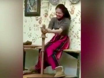 La joven no puede contener la risa al ver la figura que ha hecho con la arcilla