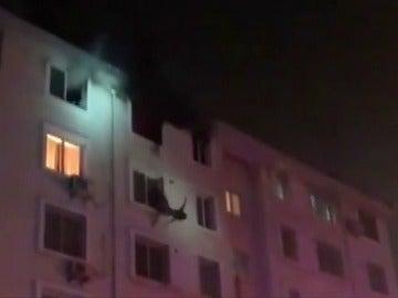 """Frame 7.304987 de: Un bombero consigue rescatar """"al vuelo"""" a una mujer cuando escapaba de un incendio por una fachada"""