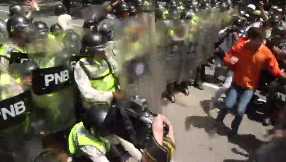 Frame 6.889486 de: La policía venezolana disuelve con gases lacrimógenos y perdigones la marcha de los opositores