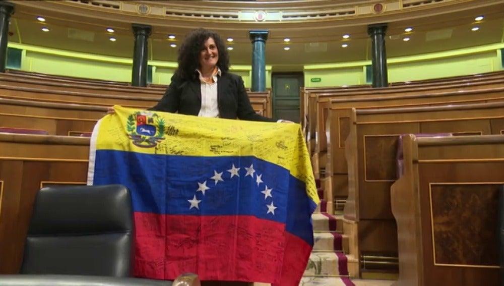 Frame 16.191149 de: Una opositora venezolana coloca su bandera en el escaño de Iglesias
