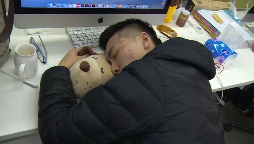 Un asiático durmiendo en el trabajo para no perder tiempo