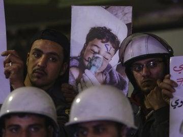 Voluntarios y personal de servicios de primeros auxilios con pancartas e imágenes de los fallecidos en el ataque químico en Siria