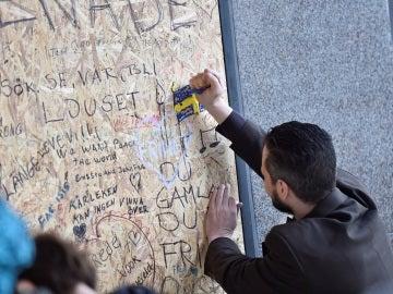 Un hombre pinta una bandera sueca en recuerdo de las víctimas