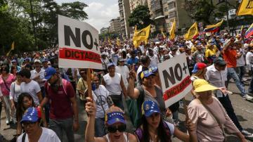 Un grupo de manifestantes quema un muñeco de trapo con la fotografía del presidente venezolano, Nicolás Maduro