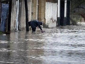 Una persona recoge agua en la puerta de su vivienda, en el barrio del Matadero de Huelva