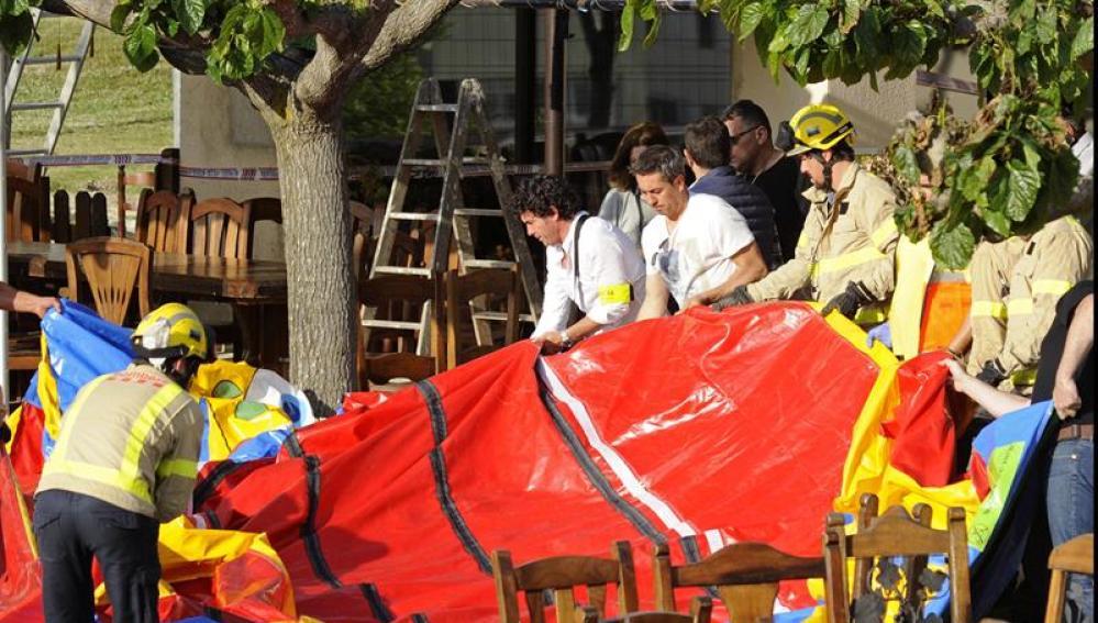 Varios operarios y bomberos retiran el castillo hinchable del restaurante Mas Oller