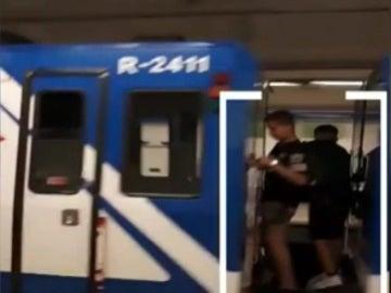 Dos niños viajan entre dos vagones del Metro de Madrid