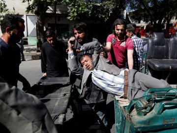 Varios ciudadanos trasladan a un herido tras el atentado
