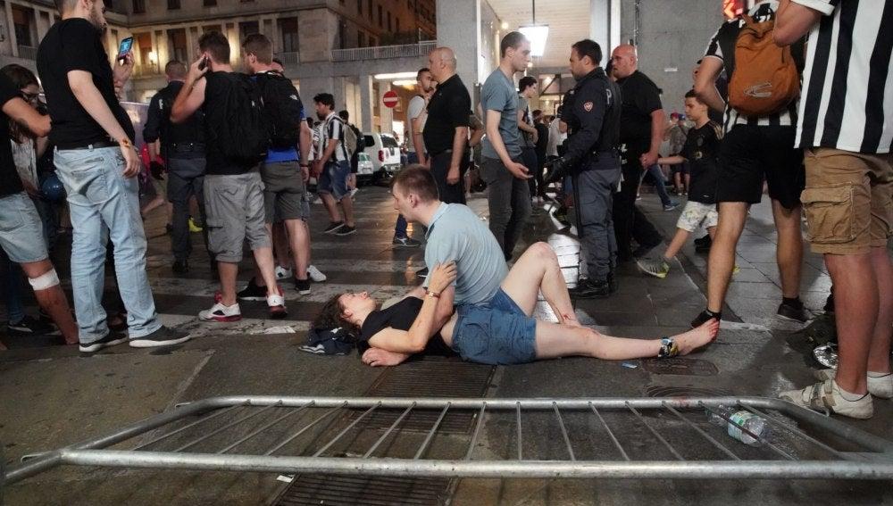 Un hombre atiende a una mujer herida tras la estampida