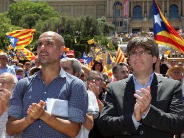 Pep Guardiola y Carles Puigdemont, aplauden al finallizar un acto con el lema 'referéndum es democracia'