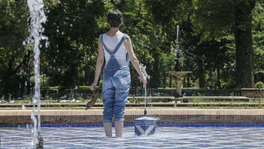 Una chica se refresca del intenso calor en una fuente del parque de Maria Luisa de Sevilla