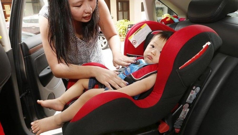 Un niño en un sistema de retención infantil en el coche