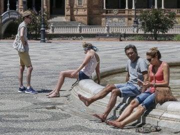 Turistas se refrescan en la plaza de España en Sevilla
