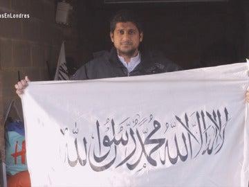 Abu Rumaysah posa con una bandera de Daesh