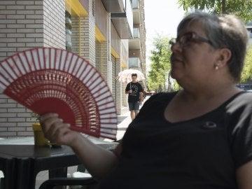 Un mujer se da aire con un abanico