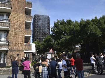 Varias personas observan la Torre Grenfell tras apagarse el incendio