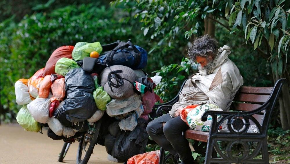 Un mendigo duerme en un banco de Londres