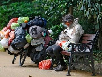 Un indigente durmiendo en un banco