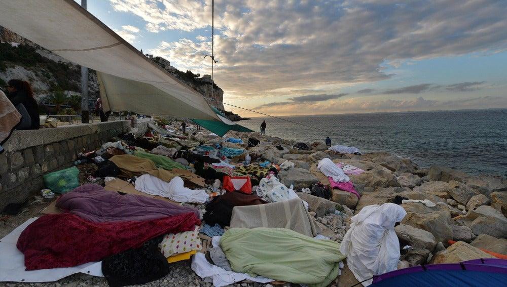 Inmigrantes duermen en la escollera de la localidad italiana de Ventimiglia, en la frontera de Francia (archivo)