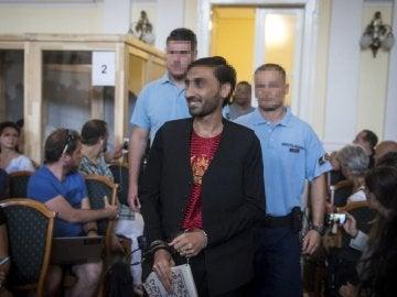 El principal acusado sonríe mientras llega a la sala del tribunal