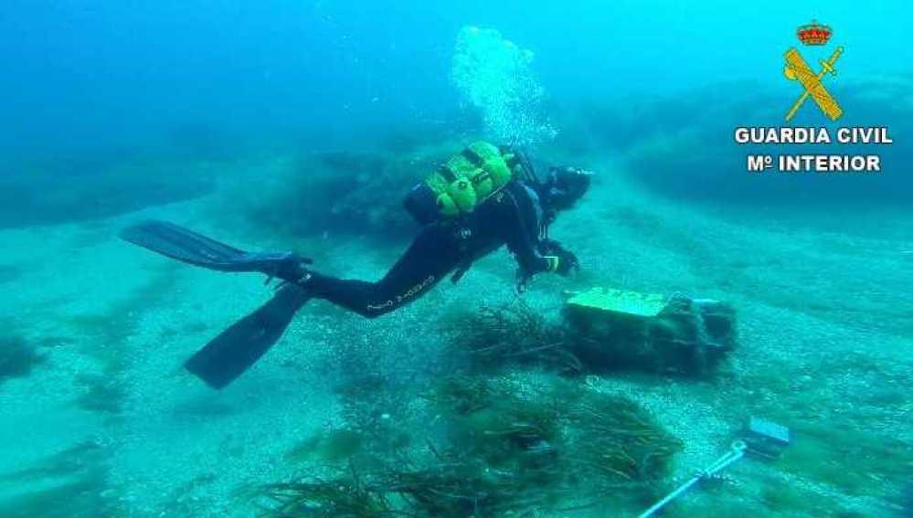 Un buzo de la Guardia Civil inspecciona el artefacto explosivo