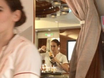 Una azafata rellena una copa de champán con los restos de otros pasajeros